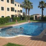 A photo of a sunny pool and apartments with two boys in the water