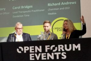 Carol Bridges talking with two panel guests at the Open Forum Events
