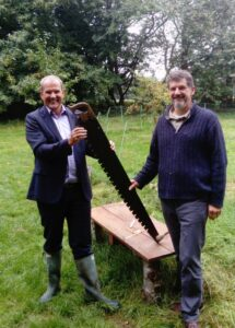 Jules Petty standing holding a saw with Graham Carpenter in garden