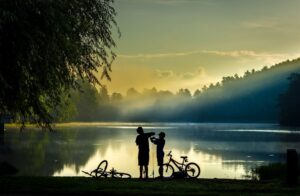 Two boys at sunset, with their bikes by a lake